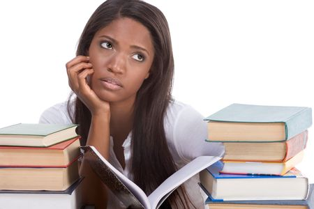 High school or college ethnic African-American female student sitting by the desk with lot of books in class or library and doing homework Stock Photo - 6357664