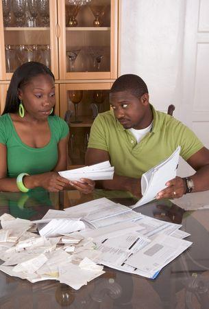 pay desk: Young black African American couple sitting by glass table and trying to work through pile of bills, frustrated by amount of expenses during economic crises recession times hoping for stimulus plan to work or expecting bailout money Stock Photo