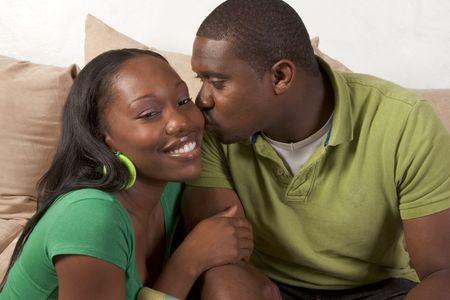 アフロアメリカン: 若いアフリカ系アメリカ人のカップルにリビング ルームに座っているソファ楽しむ時間を一緒に