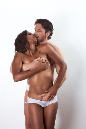 Loving affectionate nude interracial heterosexual couple in affectionate sensual hugging kissing, undressing for engage in sex. Mid adult Caucasian men in late 30s and young mulatto biracial female mix of black African American, Native American and German photo