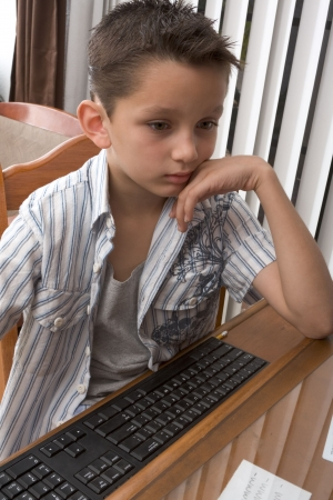 biracial: Young Multi-ethnic of Caucasian and Hispanic (Mexican) mix boy engaged in PC computer activity