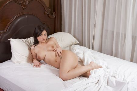 Young voluptuous brunette Caucasian woman lying down on bed