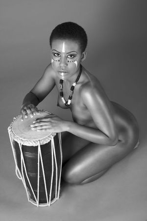 naked black women: Portrait of African American woman wearing original tribal themed face-paint and necklace playing Conga drum (toned) Stock Photo