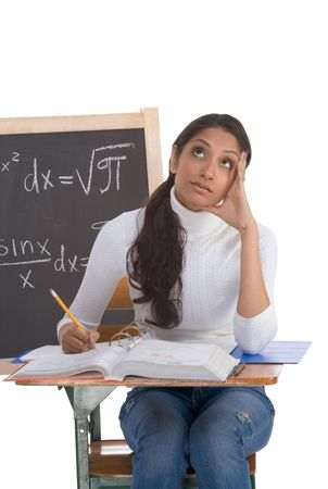 formals: High school or college ethnic Indian female student sitting by the desk at math class. Blackboard with advanced mathematical formals is visible in background