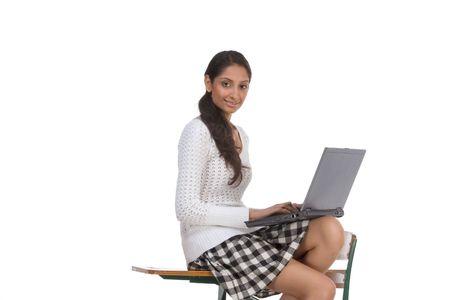 school desk: High school or college female schoolgirl student sitting on desk typing on laptop