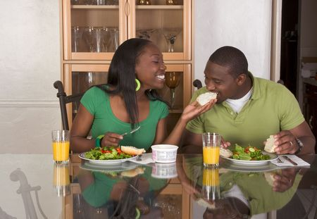 sexy food: Young black African American couple sitting by glass table and eating meal of salad, bagels with cream cheese and orange juice