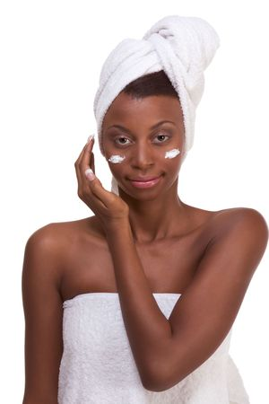 woman in bath: Skincare - Young ethnic African-American woman with slicked back hair wrapped in white bath towel applying cream moisturizer on her face after sauna