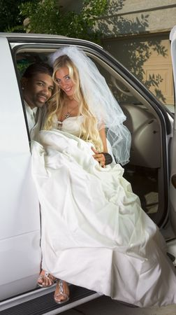 Young Caucasian happy woman in white gorgeous wedding gown sitting in car photo