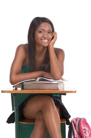 estudiante de secundaria: Escuela secundaria o la Universidad �tnica estadounidense estudiante sentado por el escritorio con libros y m�dulo de copia en clase