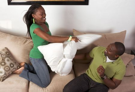 playing on divan: African-American man and woman fooling around engaged in pillow fight (motion blur)
