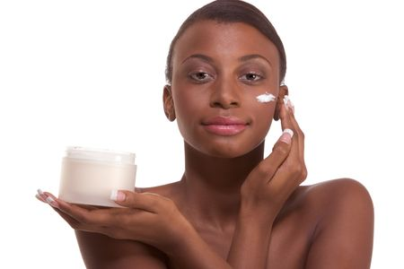 slicked back hair: Skincare - Young ethnic African-American woman with slicked back hair applying cream moisturizer on her face after sauna Stock Photo