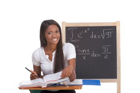 tressed High school or college ethnic African-American female student sitting by the desk at math class. Blackboard with complicated advanced mathematical formals is visible in background photo