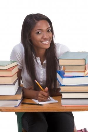 estudiante de secundaria: Escuela secundaria o la Universidad �tnica estadounidense estudiante sentado por el escritorio con gran cantidad de libros en clase o biblioteca y hacer deberes