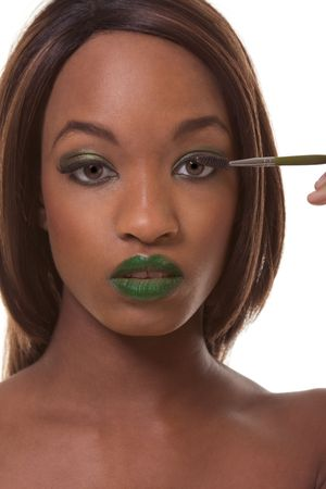 Young female beauty ethnic fashion model of African-American ethnicity with green lips and eye shades covered in dramatic make-up and holding makeup brush photo