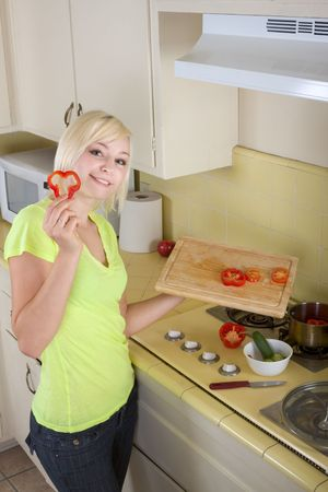 Caucasian female presenting tomatoes and lettuce holding in hands by kitchen stove range photo