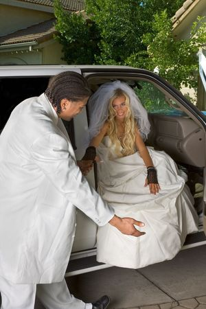 Young Caucasian happy newlywed woman in white gorgeous wedding gown sitting in car photo