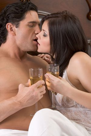 Young sexy heterosexual couple celebrating with wine in bed Stock Photo
