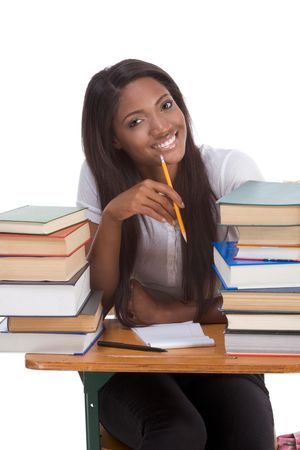 research education: High school or college ethnic African-American female student sitting by the desk with lot of books in class or library and doing homework