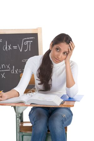 emotional stress: High school or college ethnic Indian female student sitting by the desk at math class. Blackboard with advanced mathematical formals is visible in background