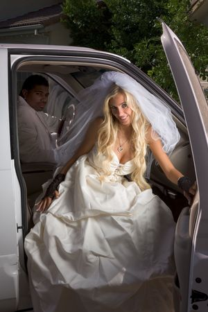 southern european descent: Young Caucasian happy woman in white gorgeous wedding gown sitting in car