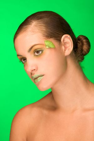 Beautiful ethnic model woman mix of Black Afro-American, Latina Puerto Rican and Italian ethnicity with kiwi fruit slice on her face photo