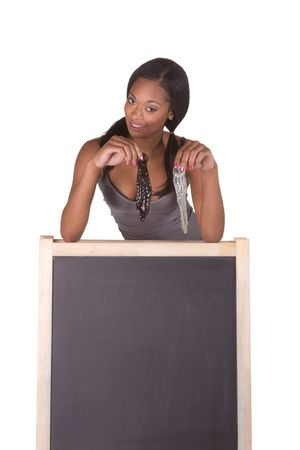 sex education: Young ethnic black female college student with white and black unrolled condom by school chalkboard. Can be used as template for sex education themed posters or invitations
