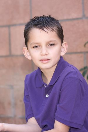 sleeve: Headshot of elementary age kid in short sleeve polo shirt. Multi-ethnic of Caucasian and Hispanic (Mexican) mix