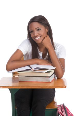 africanamerican: High school or college ethnic African-American female student sitting by the desk with books and copybook in class