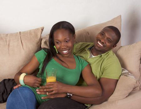 of african descent: Young African American couple sitting in living room on couch enjoying time together