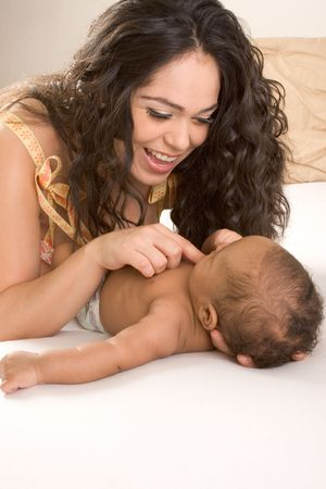 Hispanic mom lying down on bed and holding her biracial mix of Hispanic and African American infant son (baby is 7 weeks old) photo