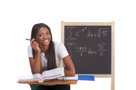 formals: Happy Friendly High school or college ethnic African-American female student sitting by the desk at math class. Blackboard with complicated advanced mathematical formals is visible in background