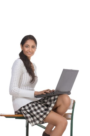 school desk: High school or college female schoolgirl student sitting on desk typing on laptop