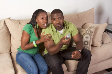 of african descent: Young African American couple sitting in living room on couch watching TV together Stock Photo