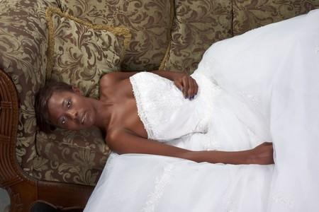 African American gelukkig vrouw in witte prachtige bruiloft jurk liggen op Bank