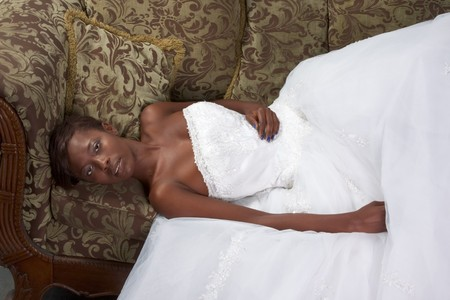 African American happy female in white gorgeous wedding gown lying down on couch 版權商用圖片