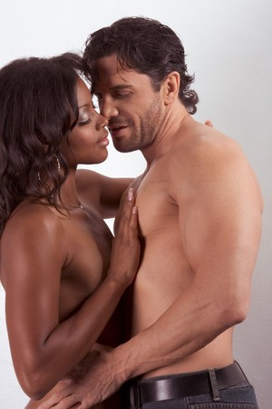 Loving affectionate nude interracial heterosexual couple in affectionate sensual kiss. Mid adult Caucasian men in late 30s and young mulatto biracial female mix of black African American, Native American and German ethnicity in 20s photo