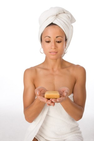 Portrait of ethnic female wrapped in white bath towel around her body and head and holding bar of soap in her palm photo