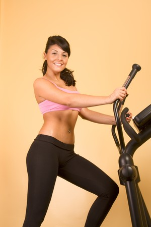Young woman sweaty while working out on elliptical machine photo