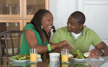 Young black African American couple sitting by glass table and eating meal of salad, bagels with cream cheese and orange juice