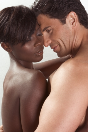 Loving affectionate nude heterosexual couple in sensual kiss and hug. Mid adult Caucasian men in late 30s and young black African-American woman in 20s Stock Photo - 8070840