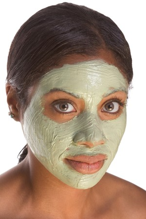 grooming product: African-American young woman relaxed with facial mask, undergoing skincare procedure Stock Photo