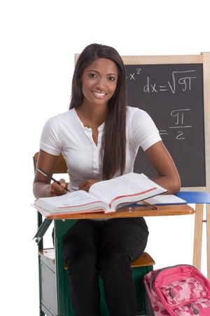 High school or college ethnic African-American female student sitting by the desk at math class. Blackboard with advanced mathematical formals is visible in background Stock Photo - 8145163