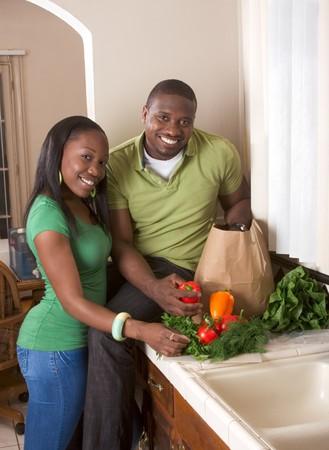 pareja saludable: J�venes negros afroamericanos par clasificaci�n vegetal en encimera de cocina  Foto de archivo