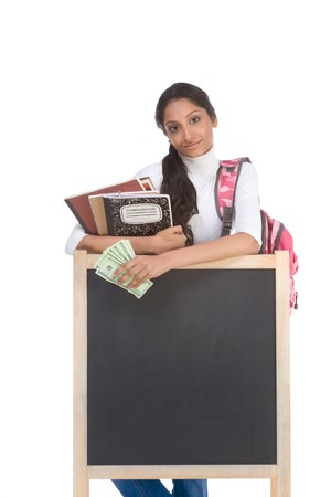 fundraiser: Template - Ethnic Indian college student with compositions notebook, copybooks and backpack by blackboard holds pile 100 (one hundred) dollar bills happy getting money help to subsidies rising costly university cost