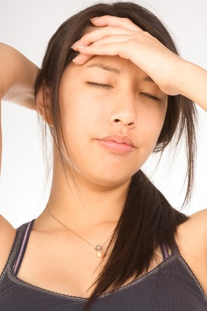 Young female squeezing her head apparently having headache photo