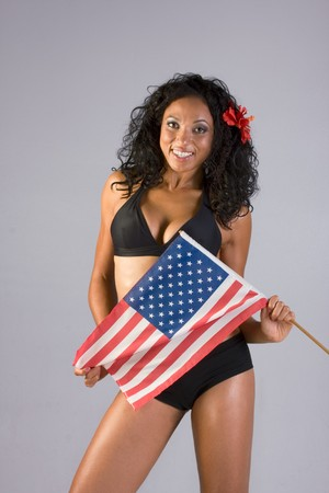 Mid aged woman in black lingerie with flower in her hair standing holding American flag in front of her photo