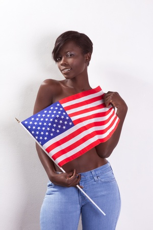 friendly dark skinned ethnic African-American girl in jeans covering her boobs by American national flag
