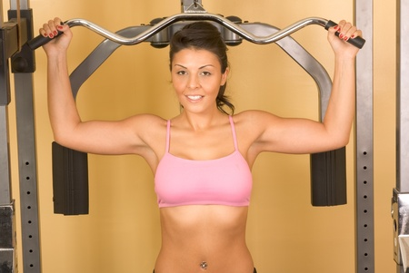 Attractive young female working out on weight-lifting training machine photo