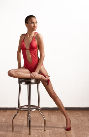 Young slender female fashion model of mixed Creole and African-American ethnicity in monokini sitting on stool with one leg stretched out and holding ankle by another hand photo