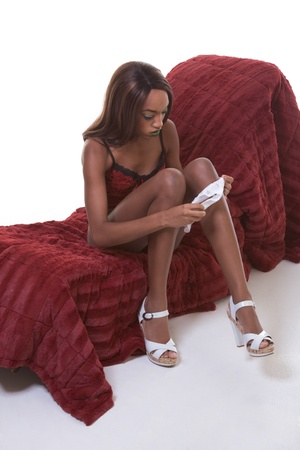 young semi naked African-American female glamour model in red lingerie sitting on couch stripping off white underwear panties Stock Photo - 8447325
